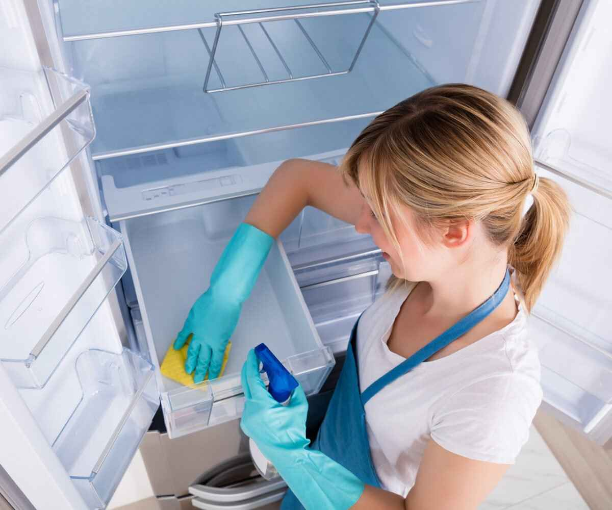 A young woman cleans out her fridge before storing it in long-term storage