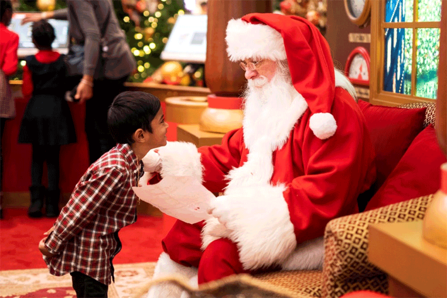 Santa and a young boy reading wish list