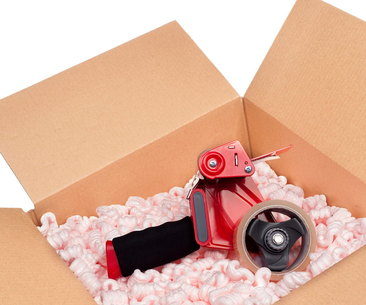 A box full of protective packaging peanuts and a tape dispenser